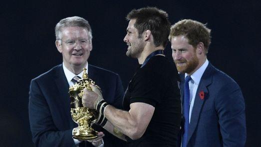 Bernard Lapasset remet le trophée de champion du monde à Richie McCaw, en 2015 sous les yeux du Prince Harry.